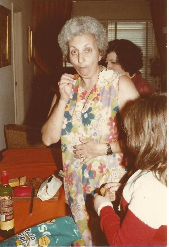 "When I think of my mama, this is who I see.  Not necessarily eating pepperoni but the woman with the silver hair (usually with a ""permanent"" because it was easier to care for) wearing a housedress (which HAD TO have two pockets so she could carry her tissues, a pack of Pall Mall red, no filters and her Bic -- people smoked inside their houses in the '70s) who hated to have her picture taken (so many photos were candids like this one) in our apartment on Barclay Avenue in Flushing."