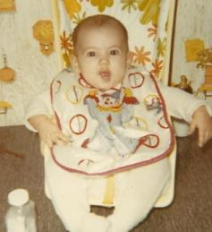 Not sure how old I am here.  Maybe 6-7 months? Smiling even with a creepy-ass clown bib on